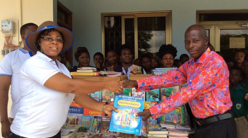 Madam Cudjoe presenting the books to the Librarian, Mr. Mawunyo