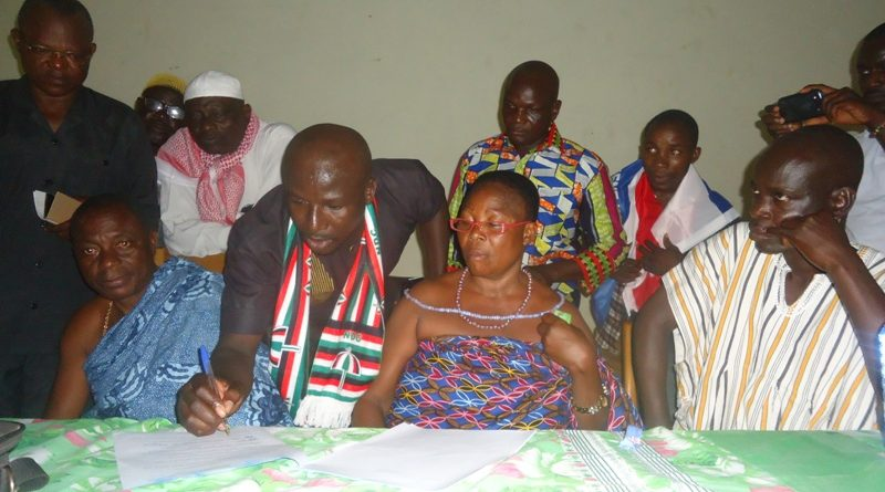 An NDC youth representative signing the MoU as other political parties' activitists and opinion leaders look on