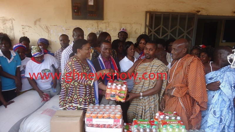 Mrs. Akufo-Addo presenting the Homowo item to Nii Obli. Looking on are some NPP supporters and members of the Kpone Traditional Council