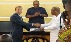 Ghana's Health Minister receives the assistance as President Mahama looks on.