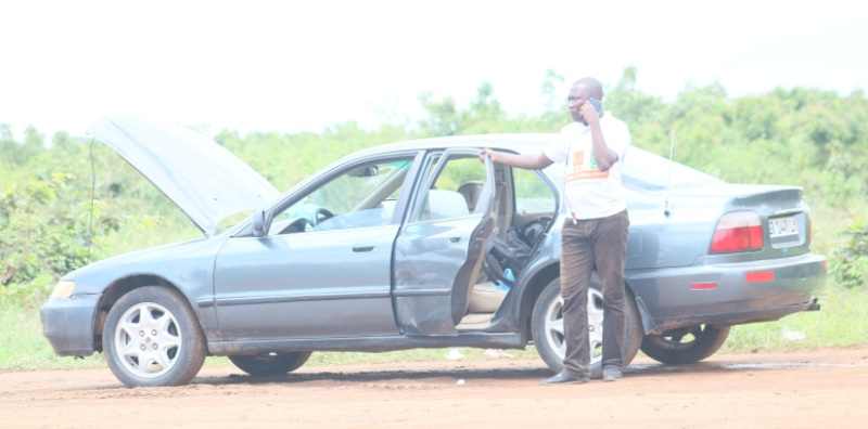 A-first-time-driver-on-the-Doryumu-road-standing-by-his-broken-down-vehicle-after-his-car-engine-had-been-submereged-in-a-pool-on-the-stretch.